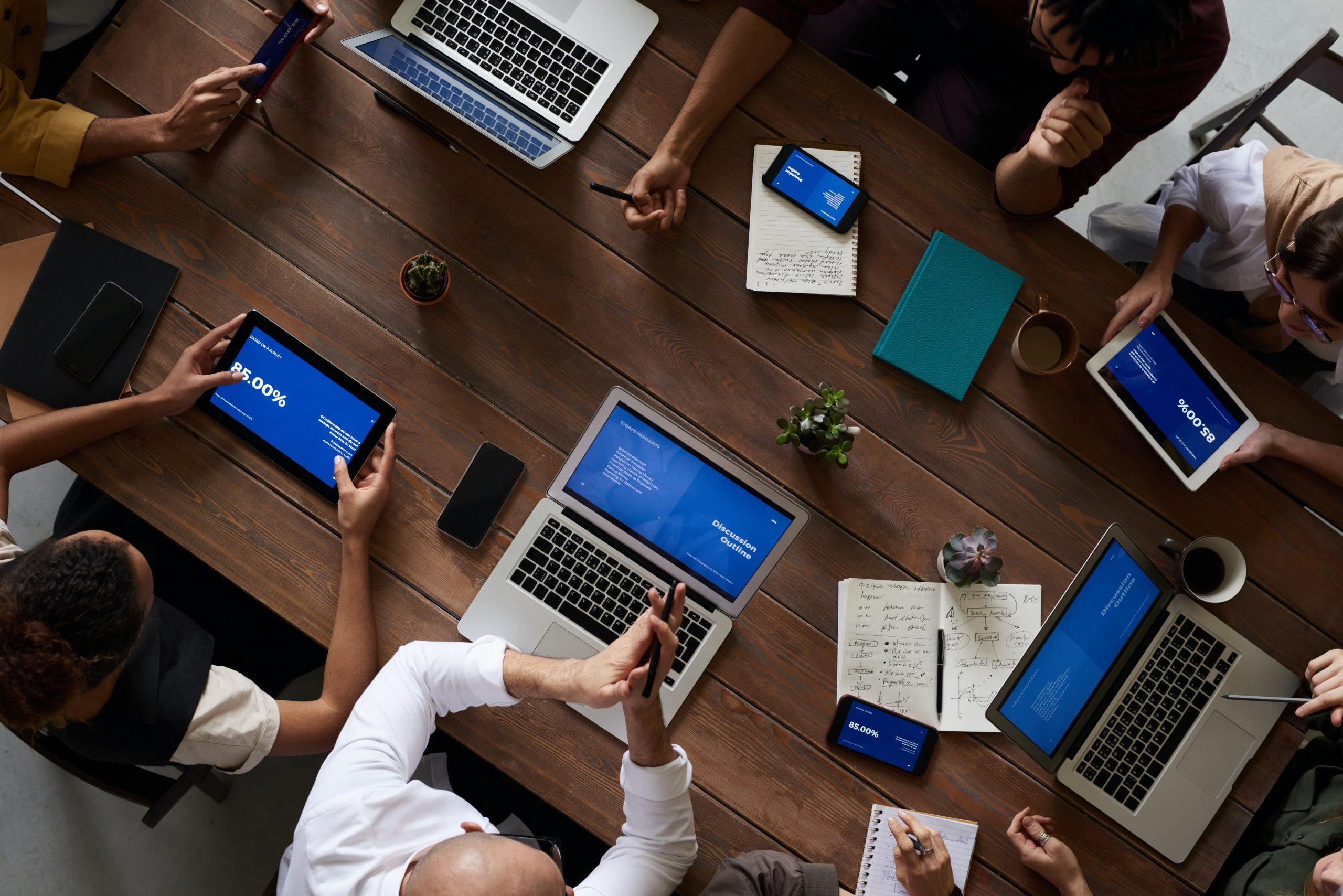 Imagem mostra uma sala na qual várias pessoas usam seus notebooks.