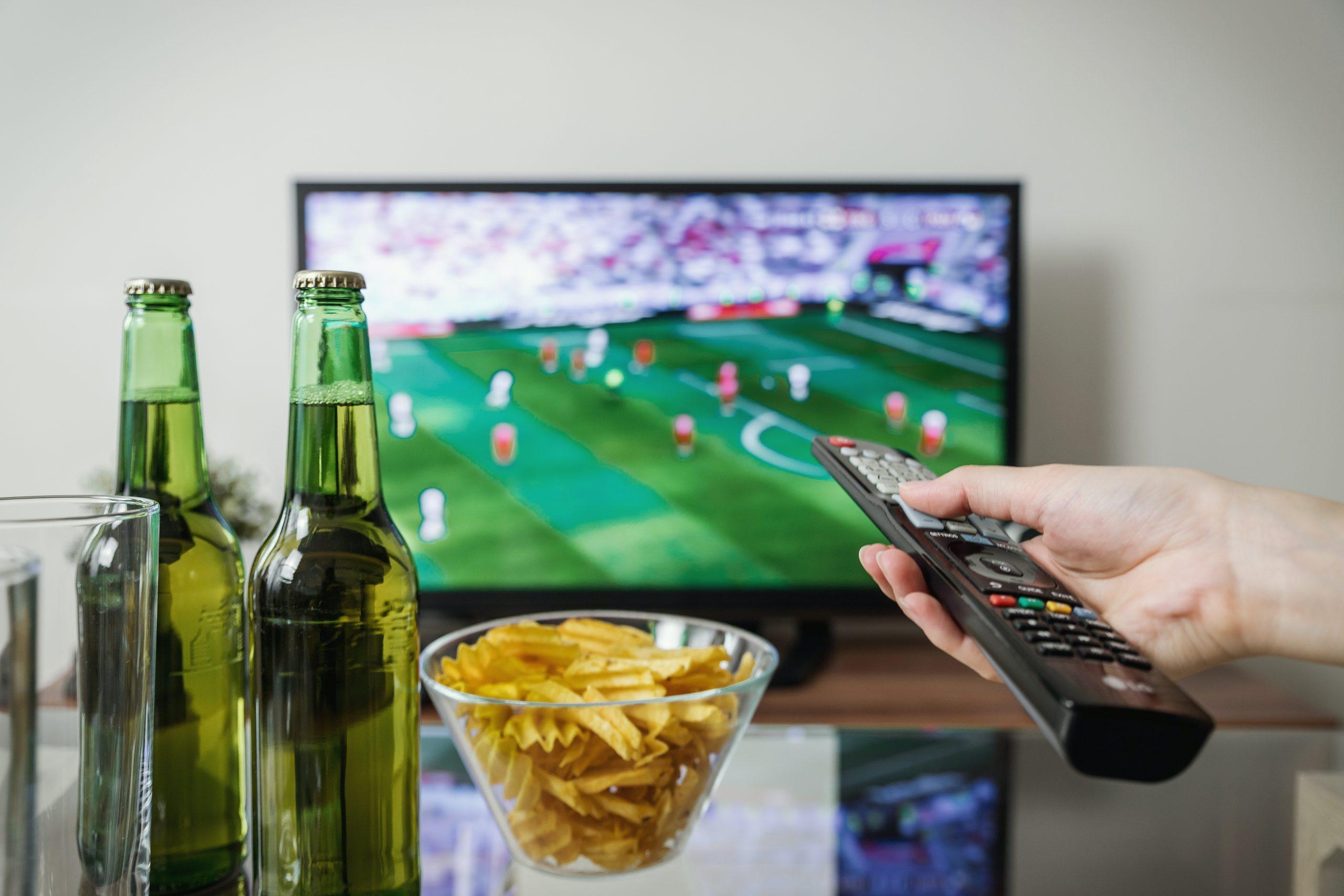 Imagem mostra uma televisão exibindo futebol ao fundo de uma mesa com cervejas e petiscos.