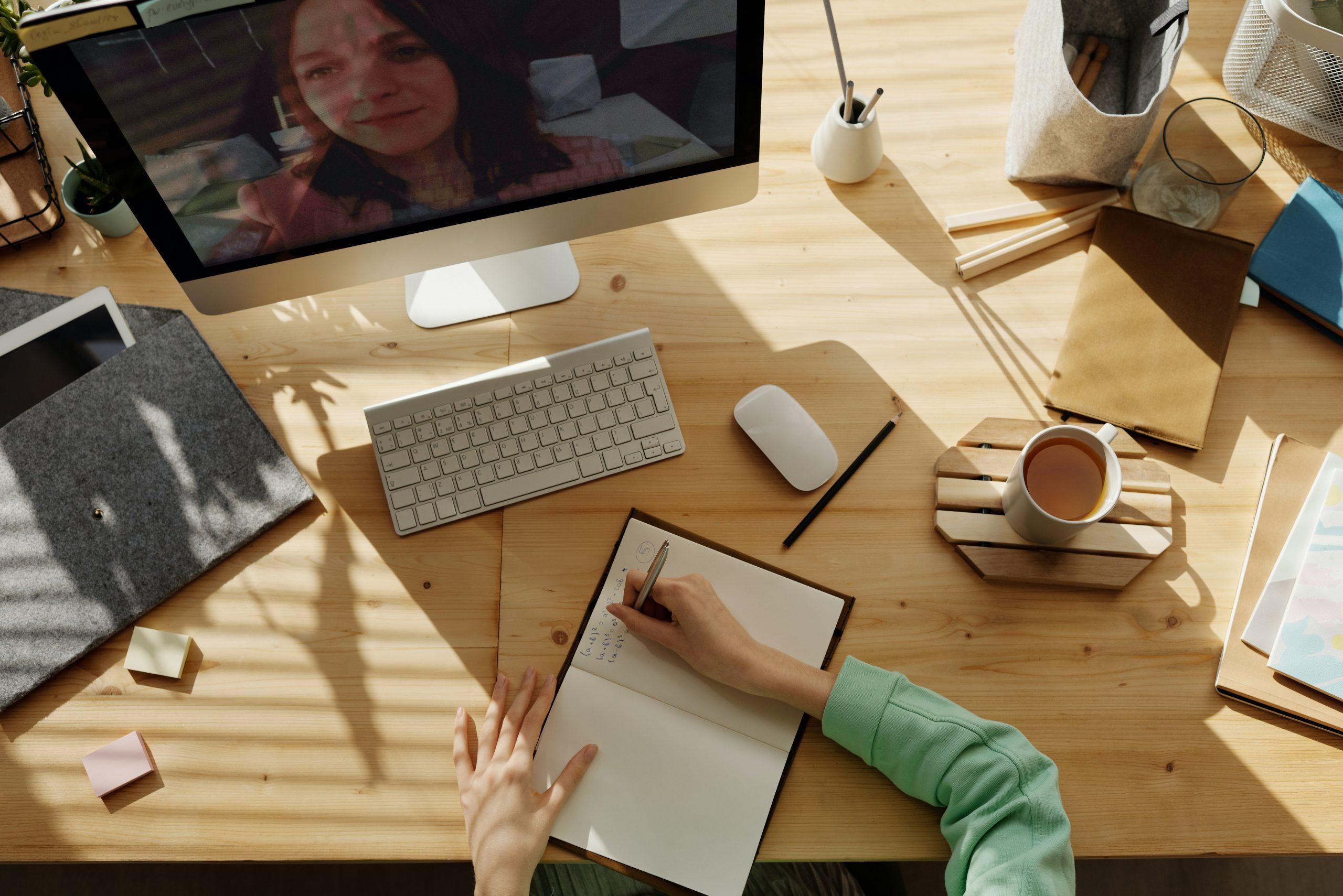 Imagem mostra uma mulher fazendo anotações em frente ao computador.