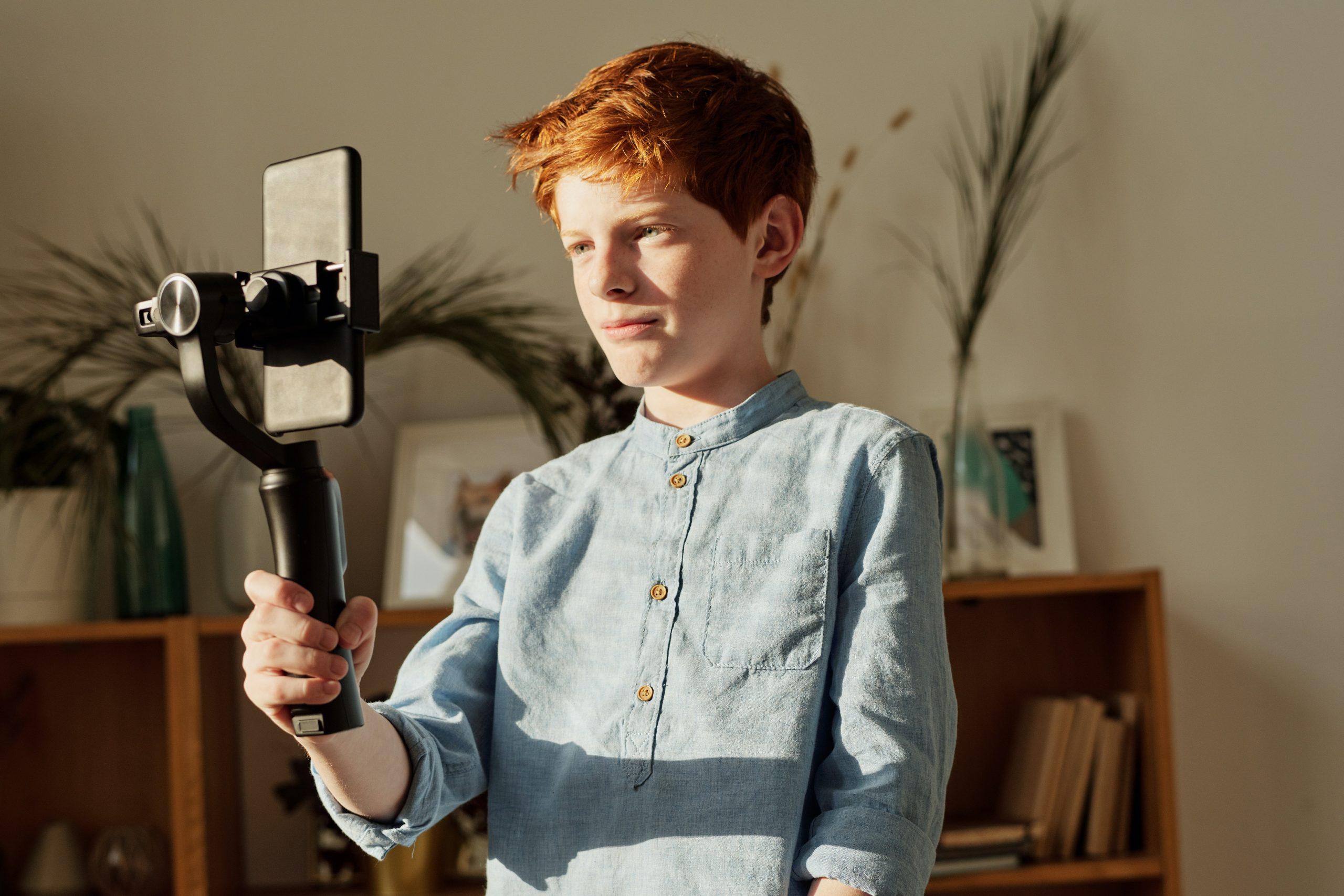 Imagem de um garoto segurando um bastão de selfie.