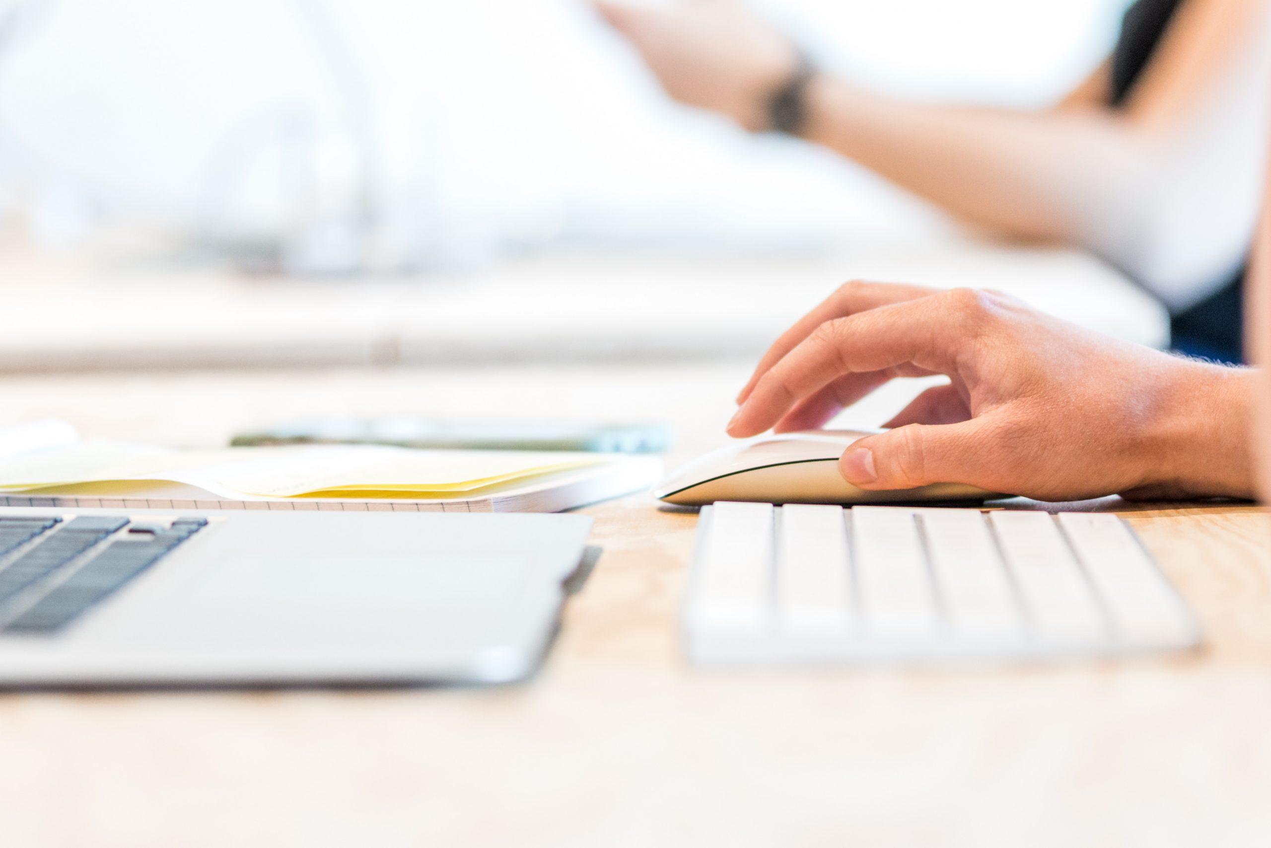 Imagem mostra uma pessoa usando teclado e mouse sem fio com um MacBook.