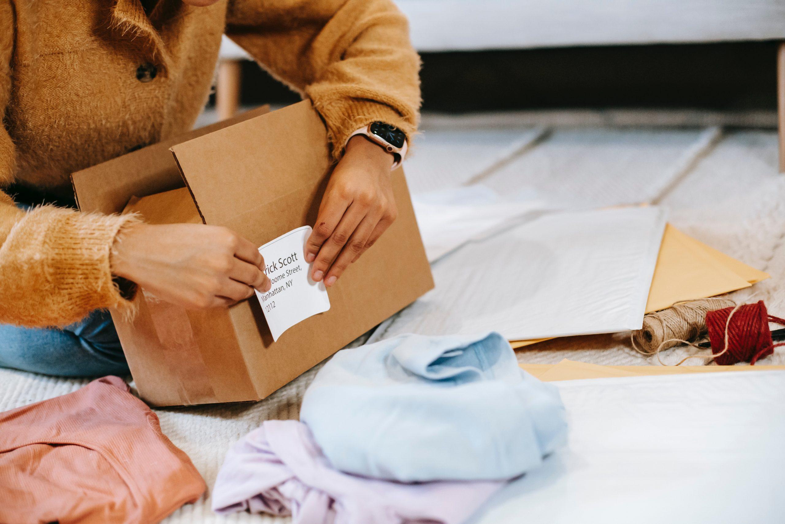 Imagem de uma mulher etiquetando uma caixa de papelão.