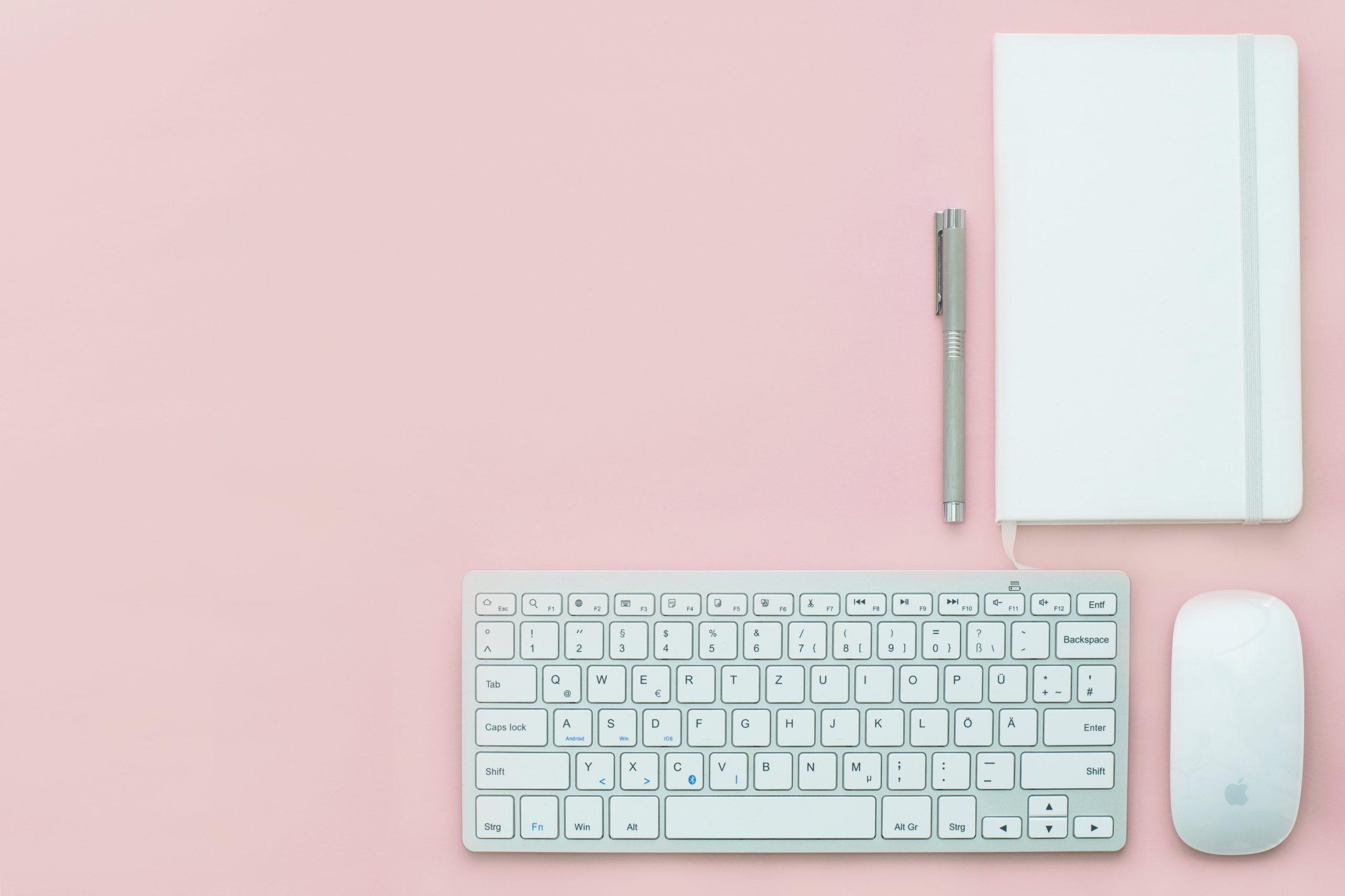 Imagem mostra um teclado e um mouse da Apple junto a uma caderneta.