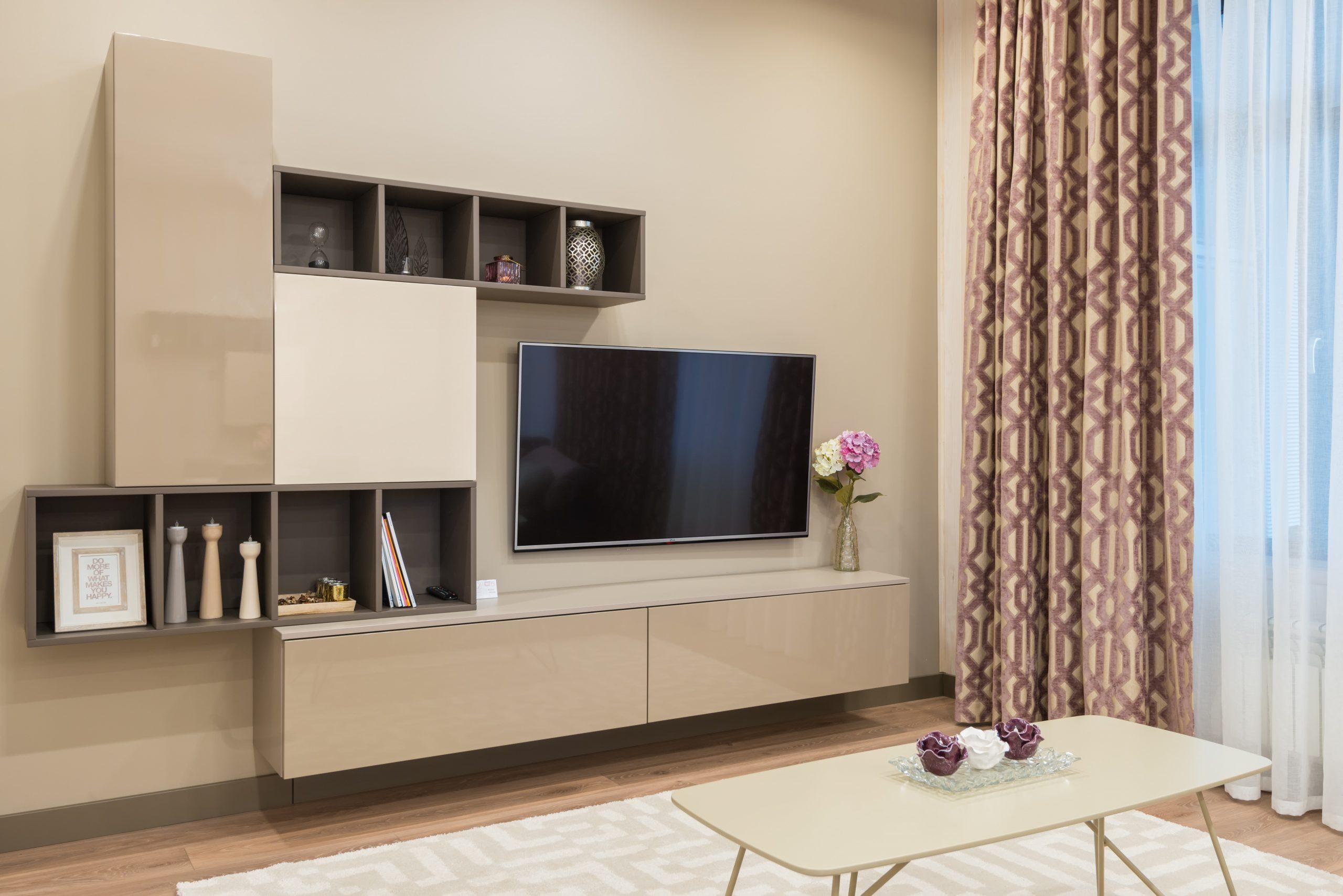 Imagem mostra uma sala completa com televisão.