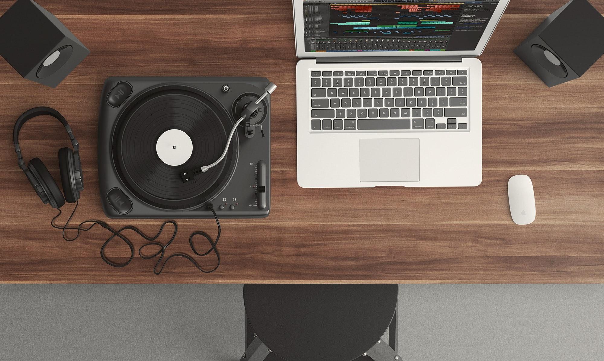 Imagem mostra um mouse sobre uma mesa ao lado de um notebook e equipamentos de som.