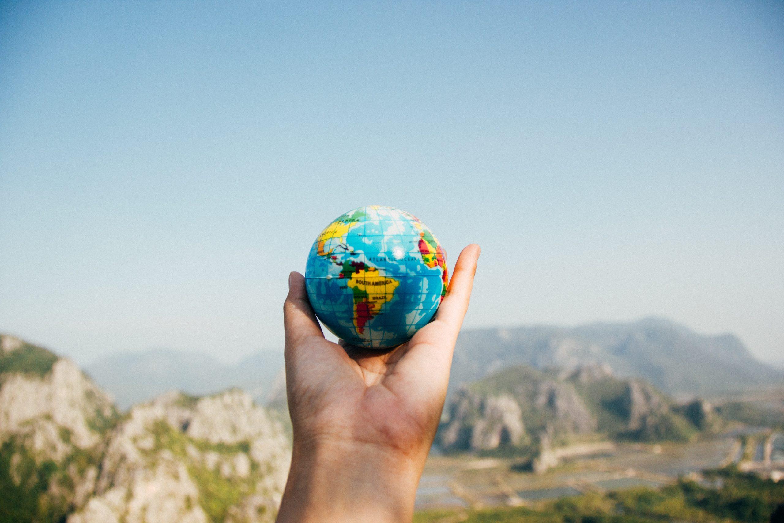 Imagem mostra uma pessoa segurando um globo terrestre.