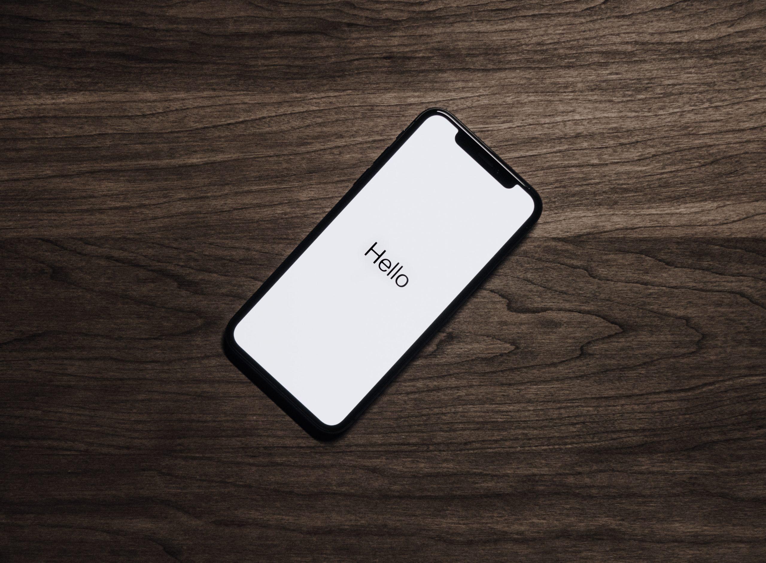 Imagem mostra um Iphone em sua tela inicial sobre uma mesa.