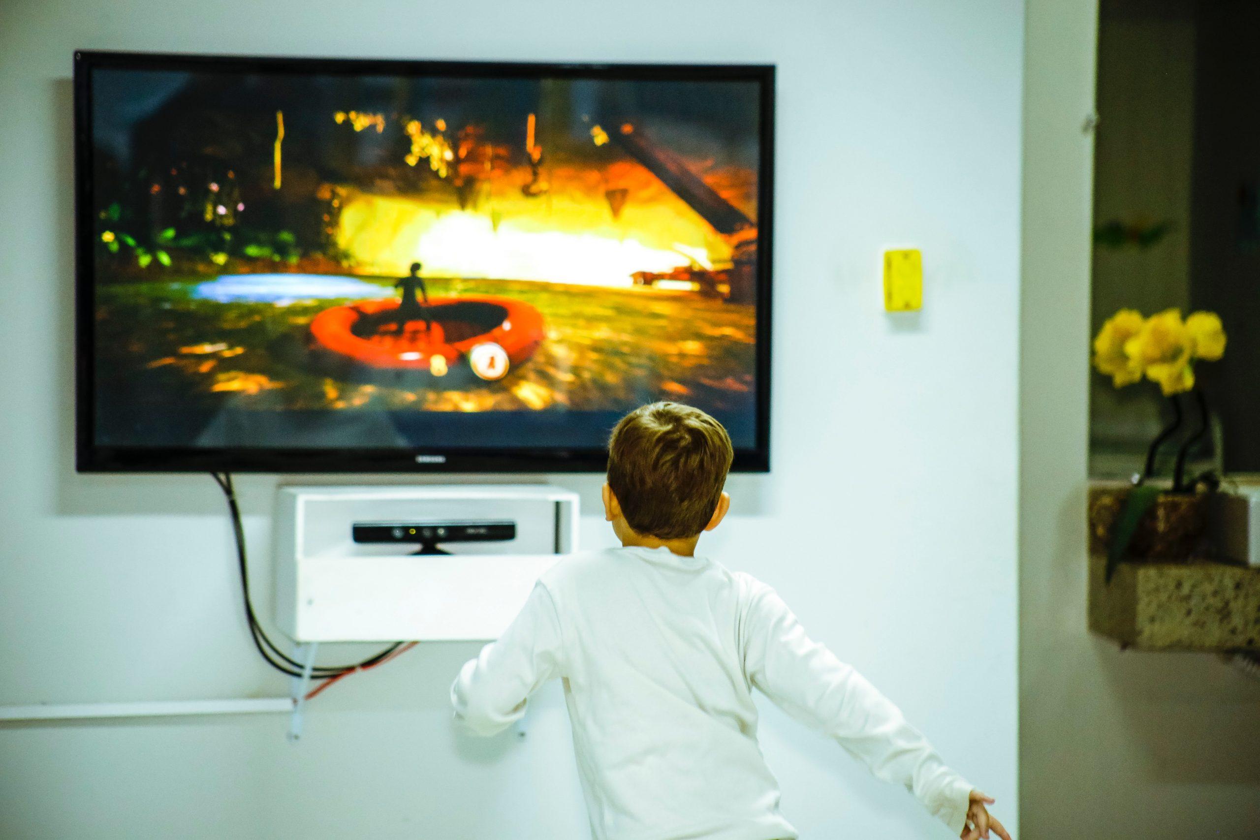 Imagem mostra uma criança jogando videogame em uma grande TV.