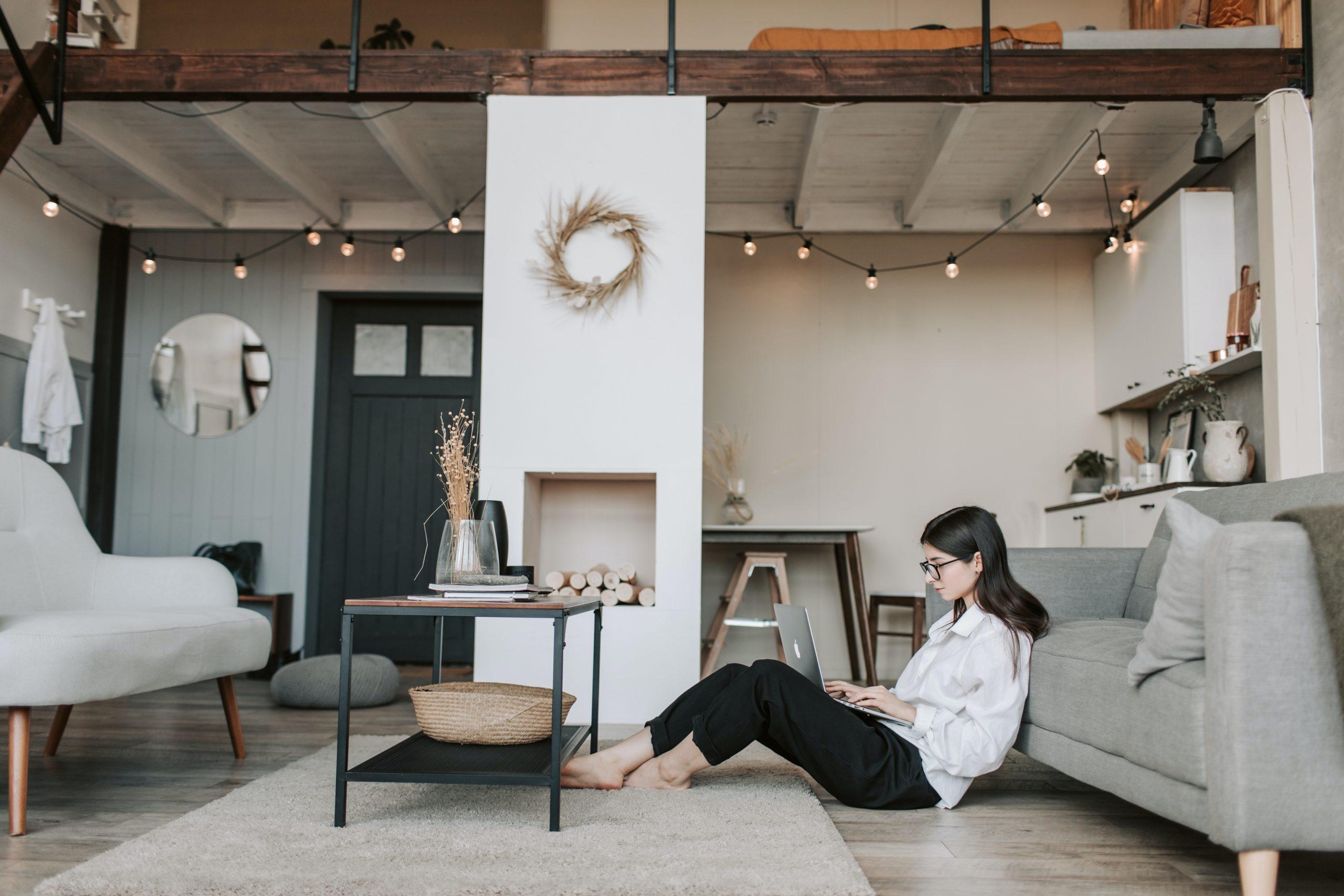Imagem mostra uma mulher sentada no chão usando um computador.