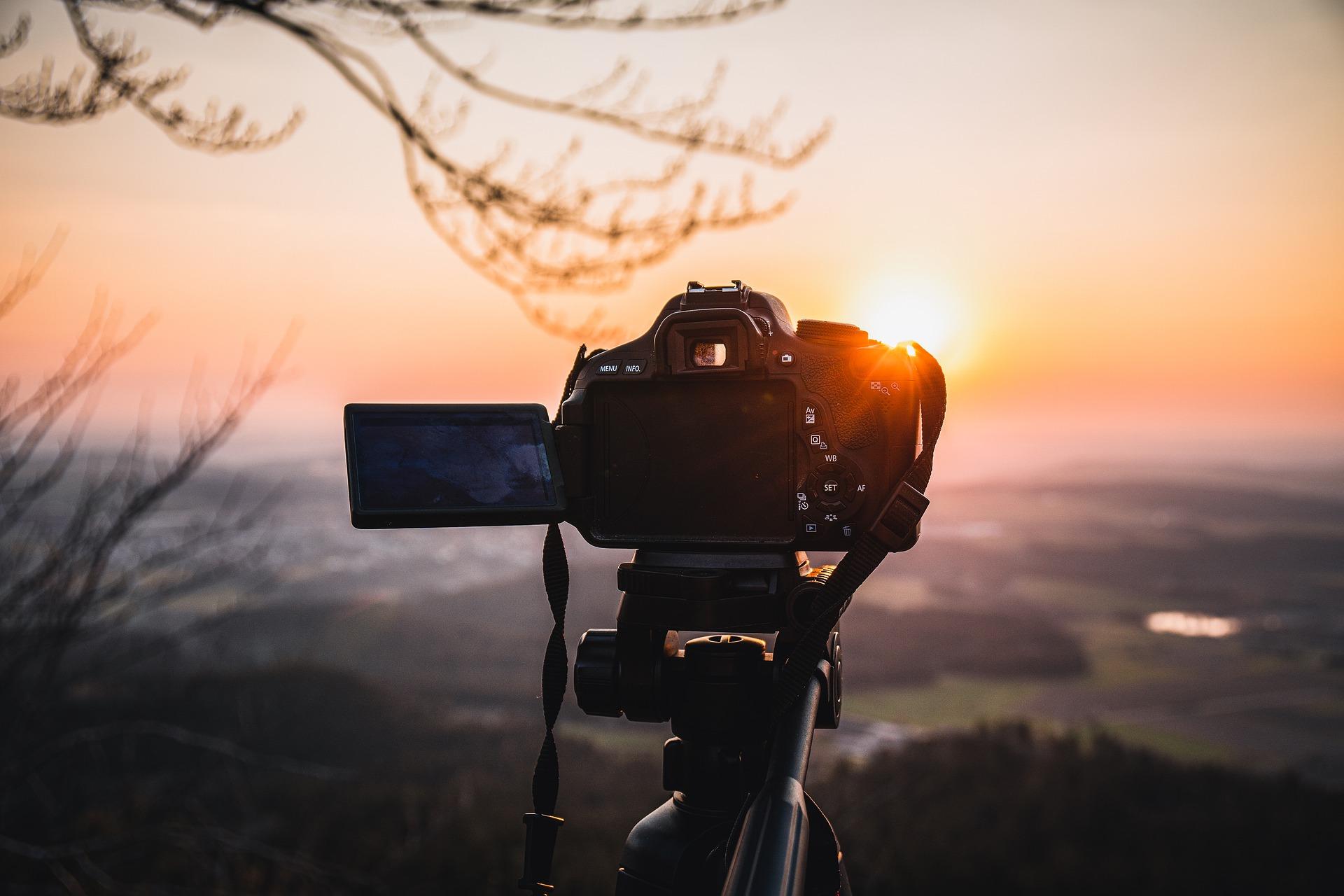 câmera apoiada em um tripé registrando o pôr-do-sol