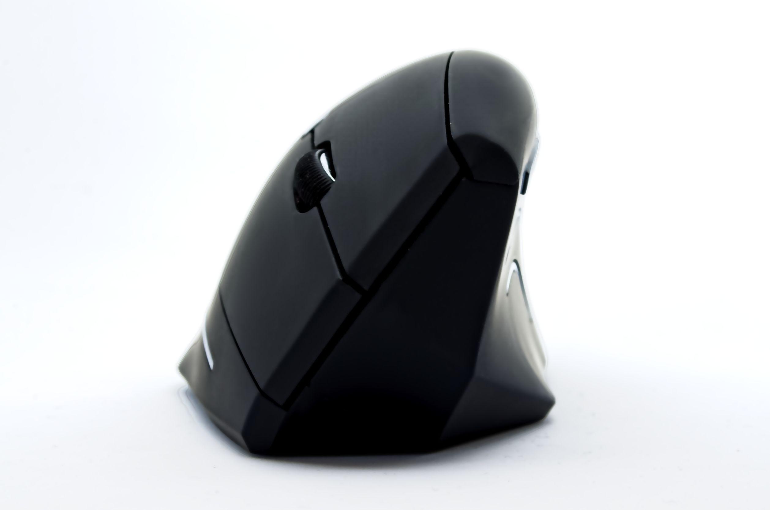 Imagem mostra um mouse vertical sobre um notebook.