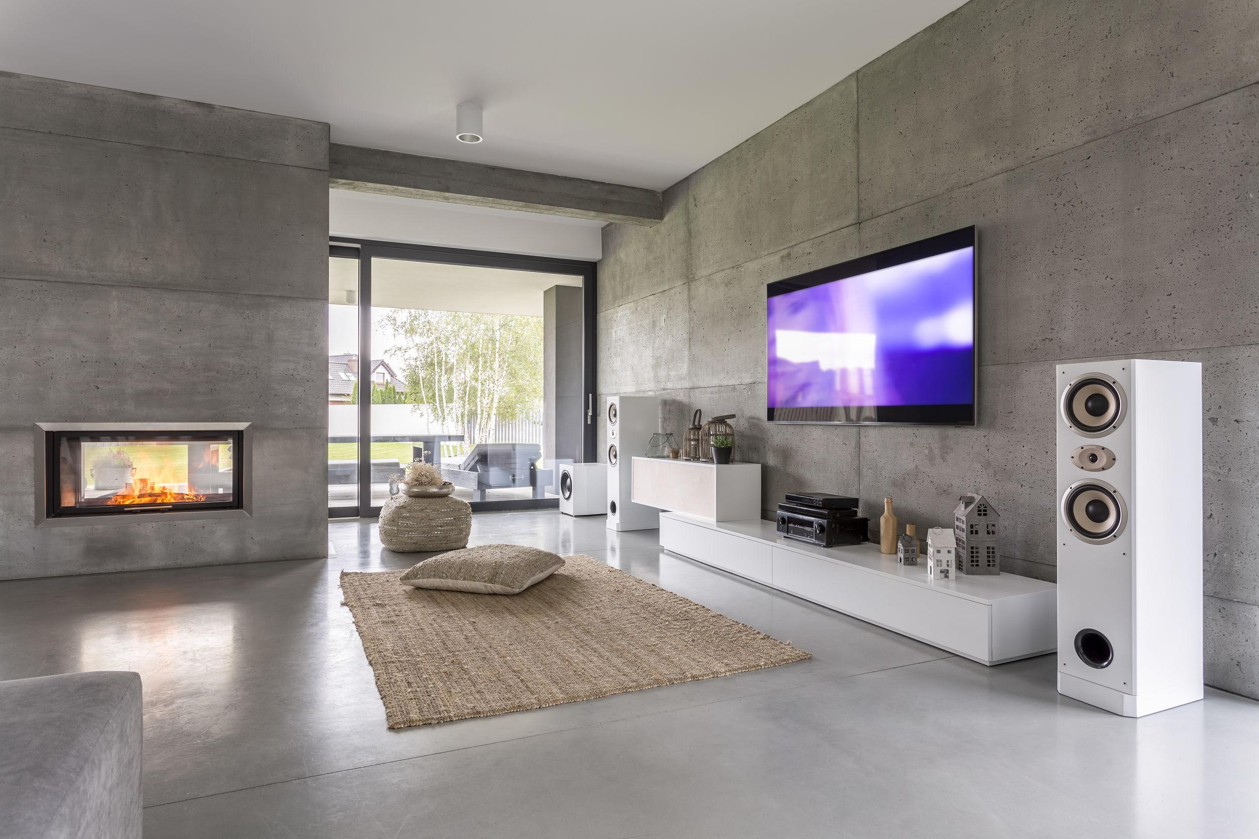 Televisión salón con ventana, chimenea y efecto muro de hormigón