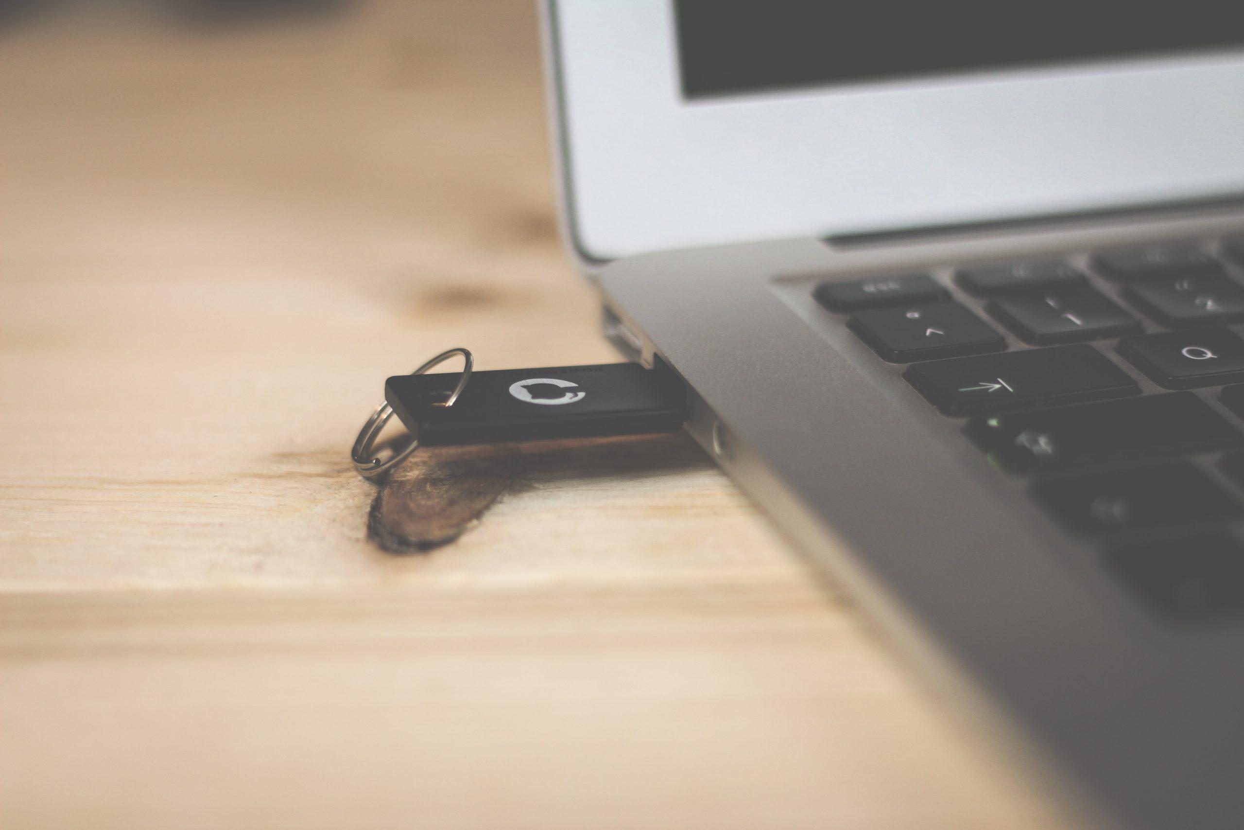 Imagem mostra um notebook com adaptador USB conectado.