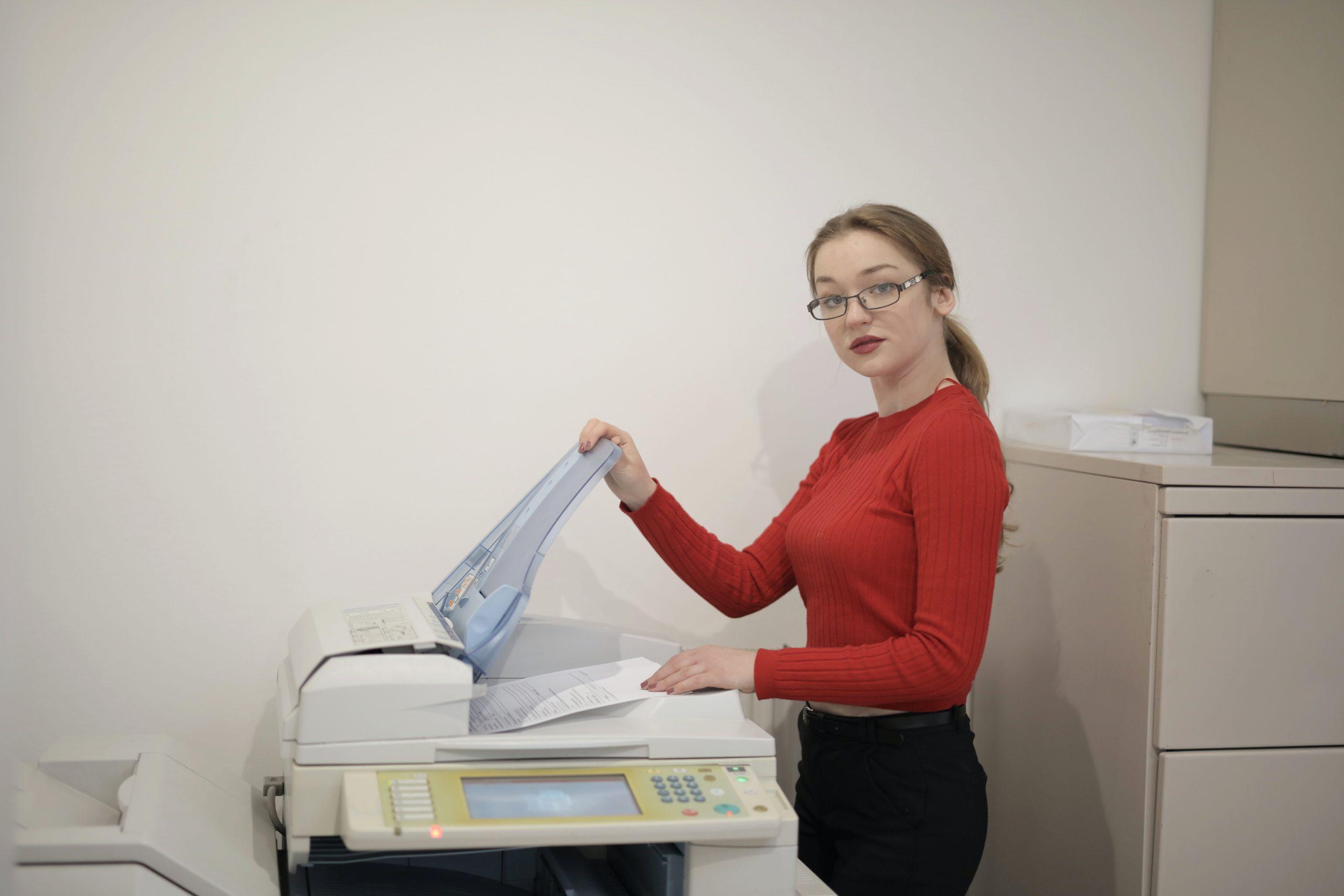 Imagem mostra uma mulher usando uma impressora em um escritório.