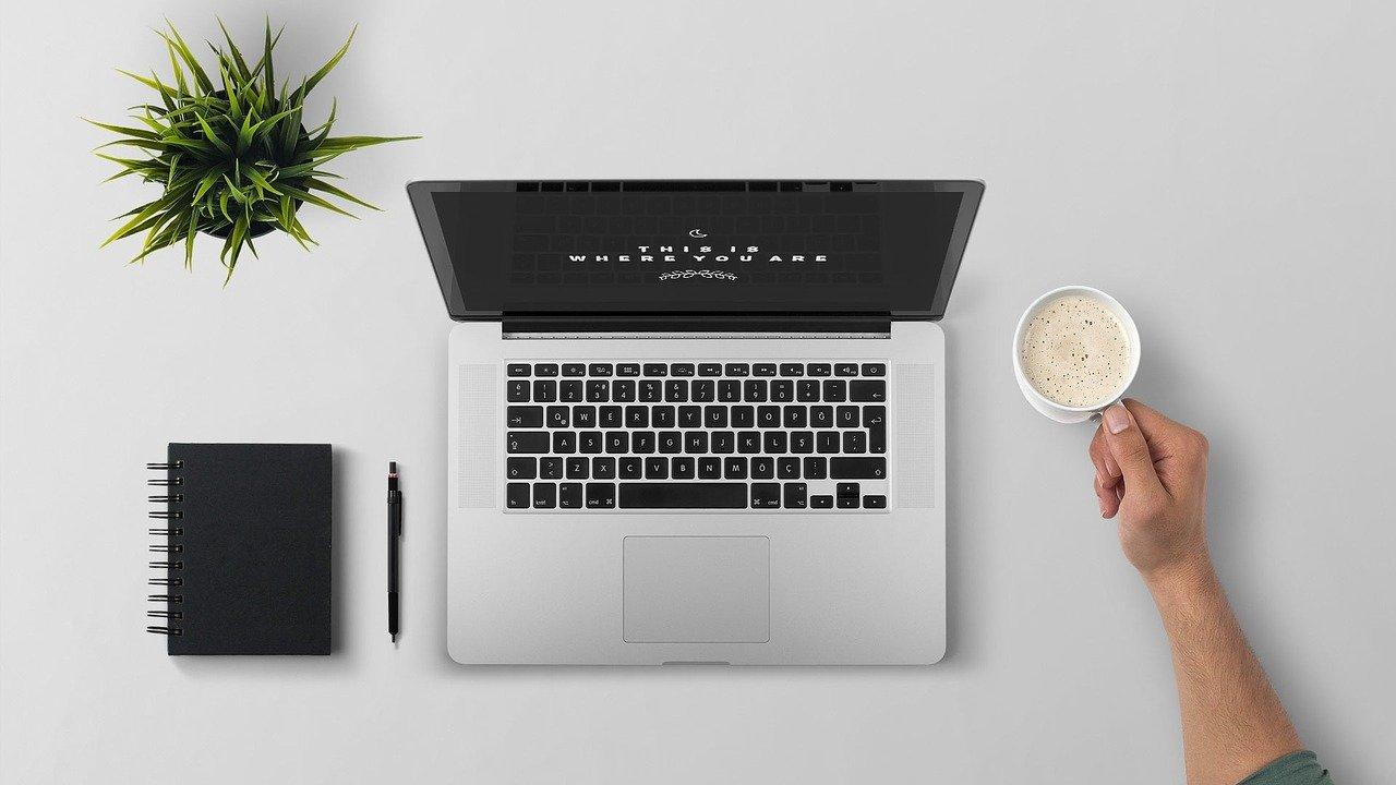 Imagem mostra o braço de uma pessoa que usa um notebook sobre uma mesa.