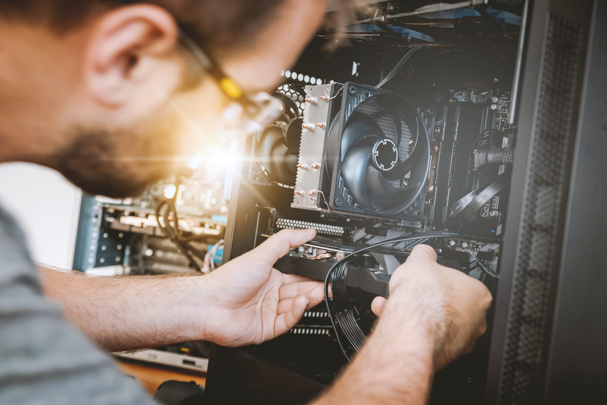 Imagem de um homem realizando a manutenção de um computador.