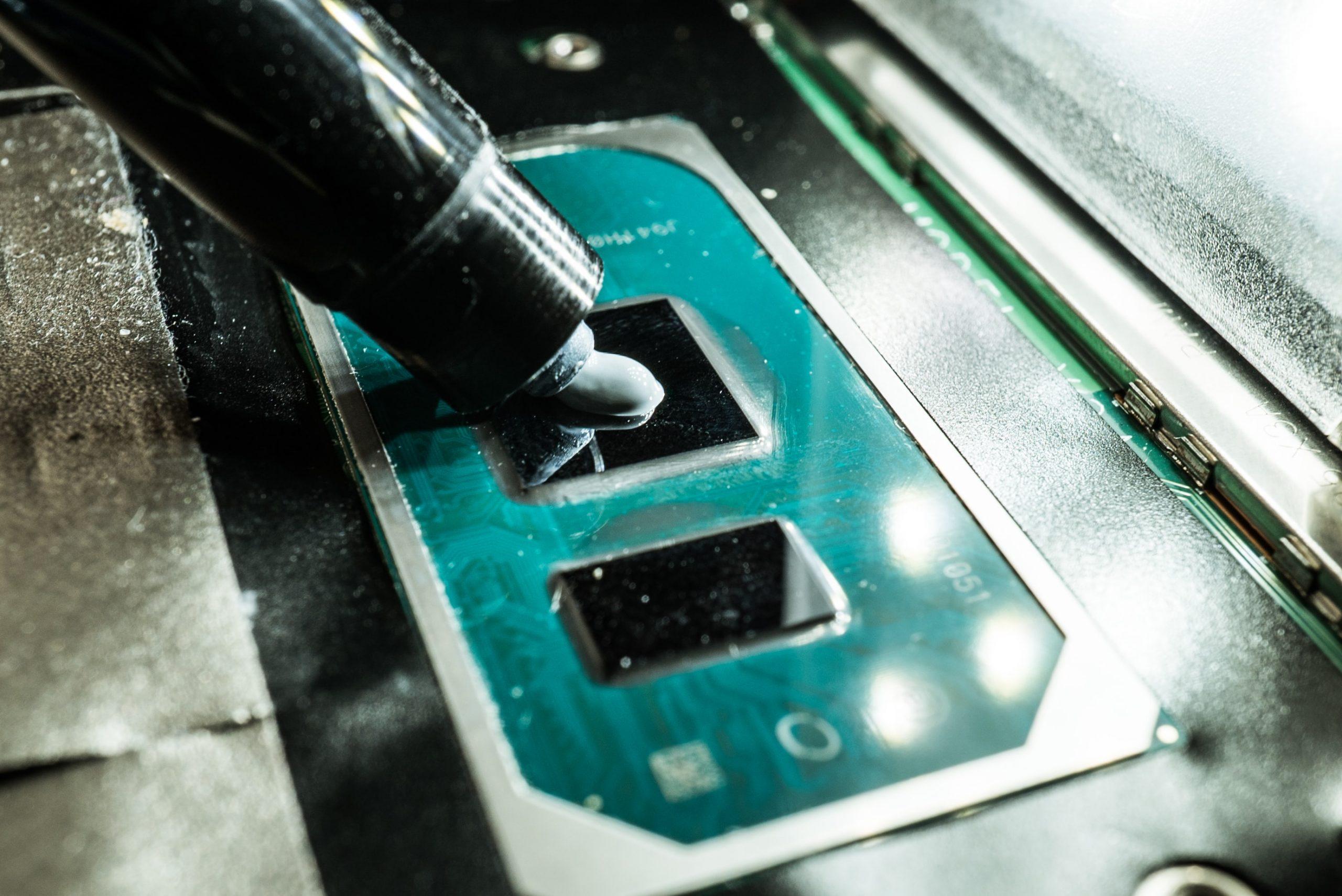 Imagem mostra uma pessoa aplicando pasta térmica em um processador.