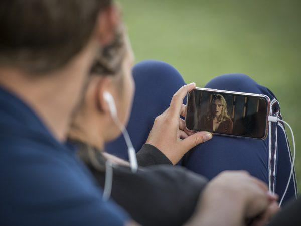 Imagem mostra pessoas assistindo a um vídeo no celular.