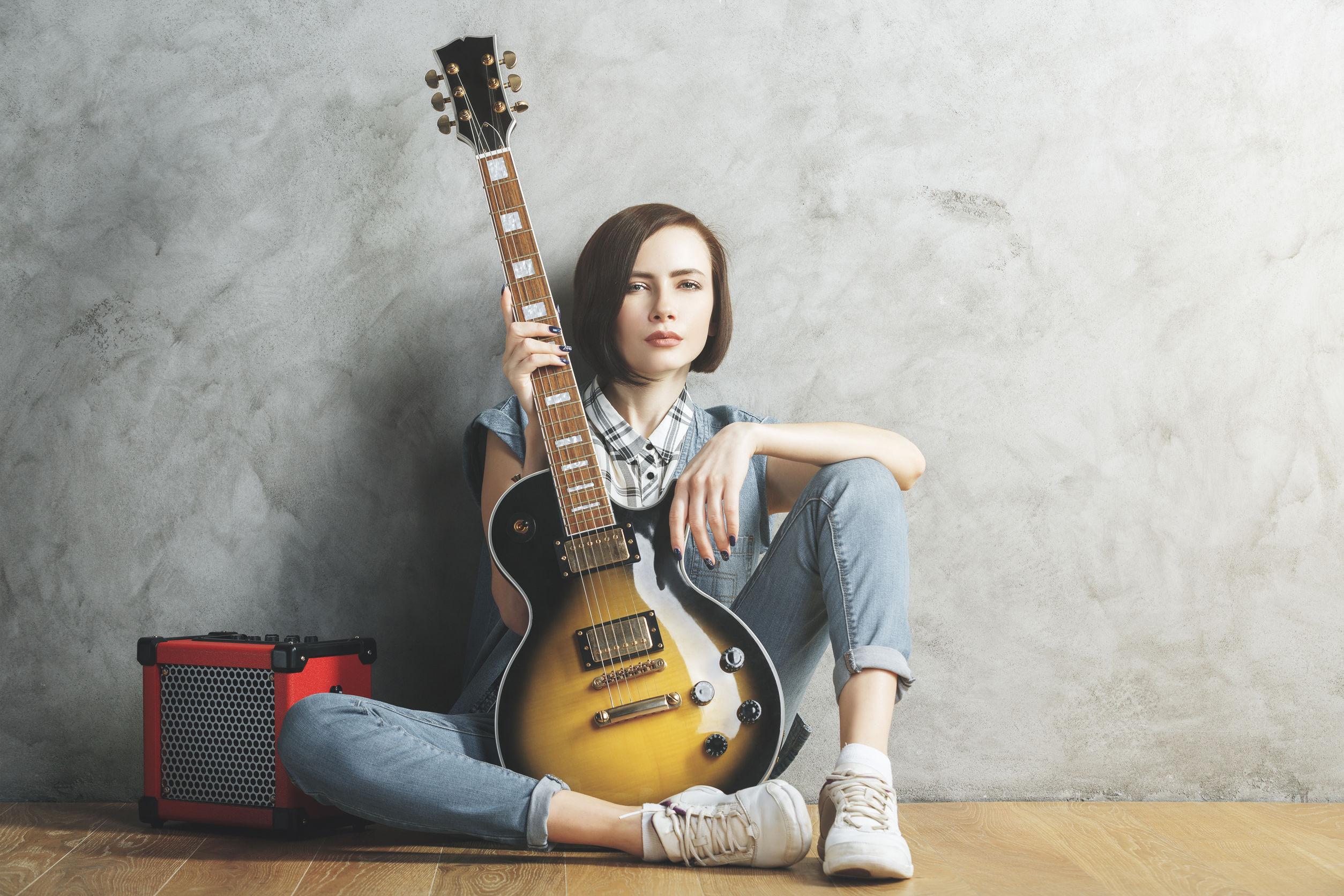 Mujer bonita con la guitarra eléctrica y el amplificador