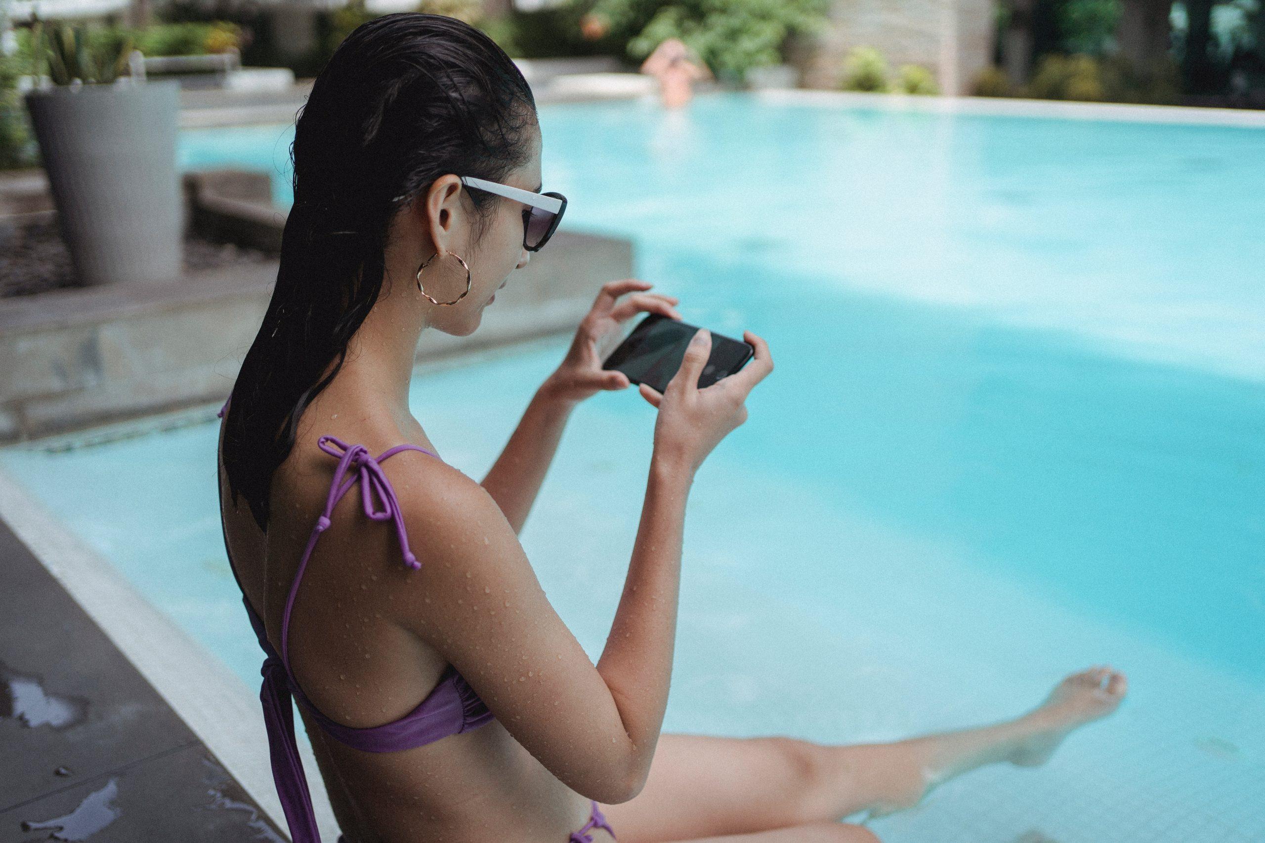 Imagem de uma mulher usando o celular na beira da piscina.