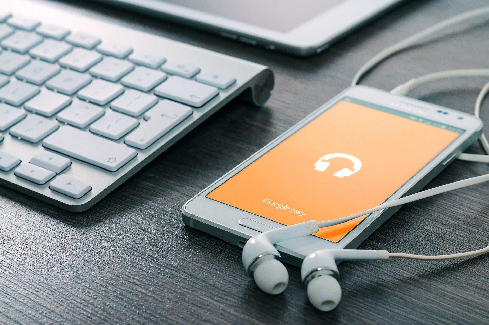 Imagem mostra um celular sobre uma mesa com fone de ouvido conectado.