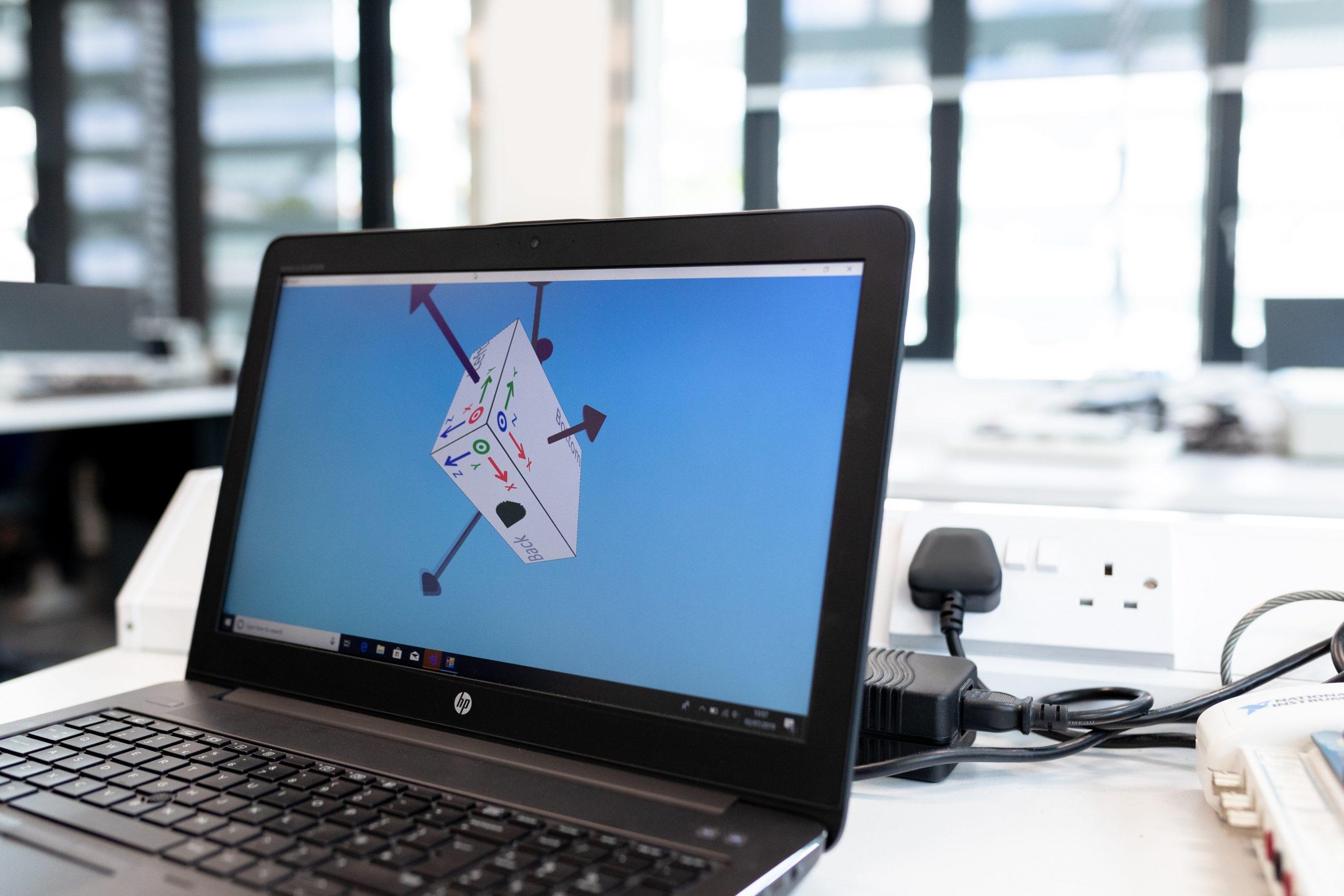 Imagem mostra um notebook e seu carregador mais ao fundo.