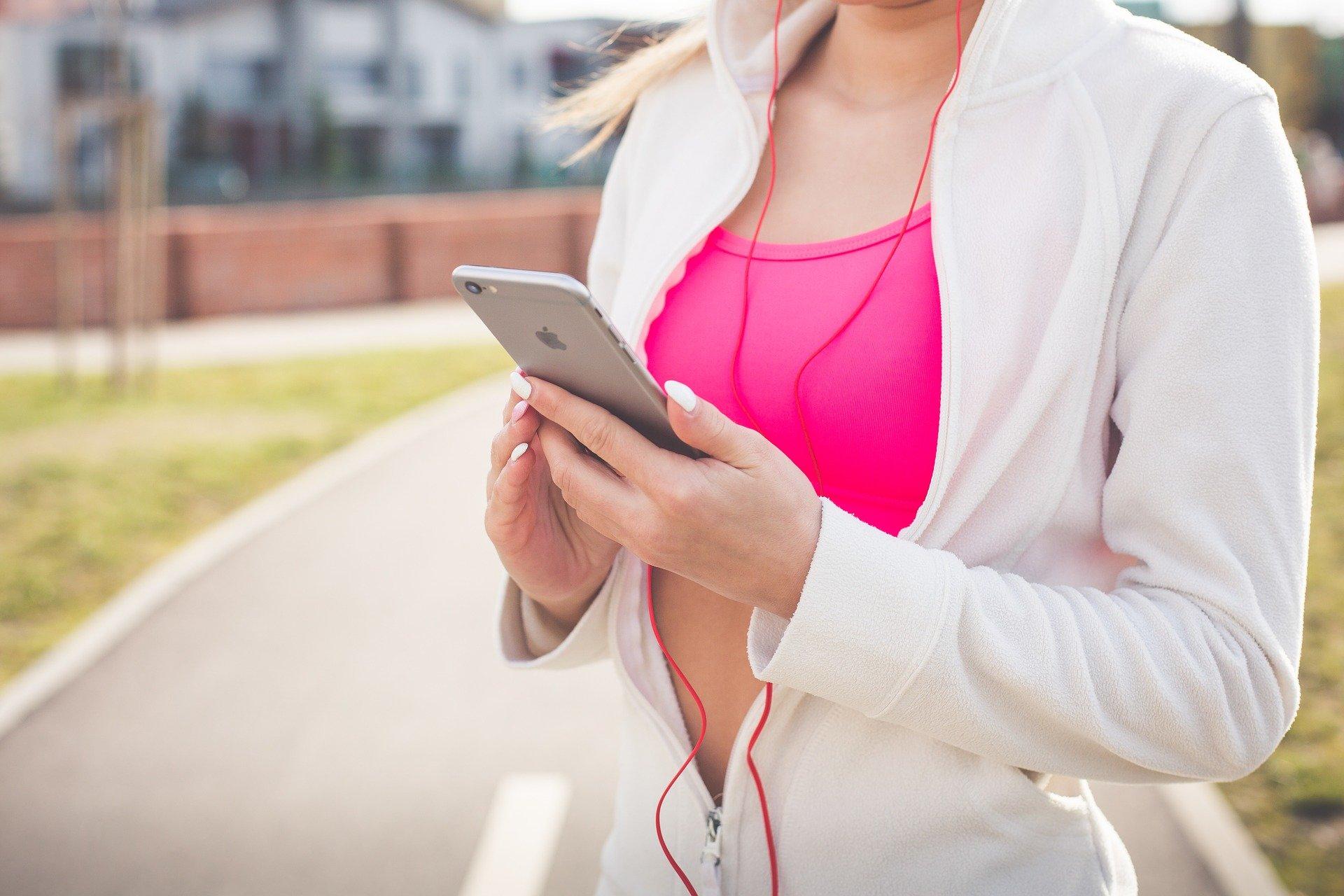 Imagem mostra uma mulher na rua usando celular com fone de ouvido.