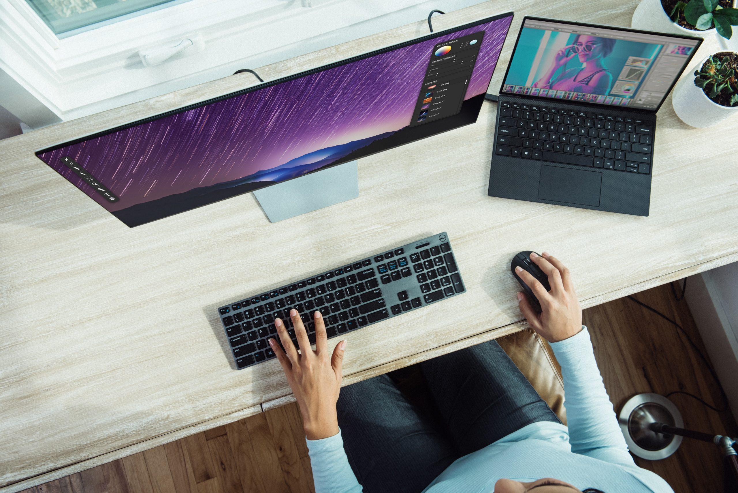 Imagem de uma mulher utilizando um computador e um notebook.