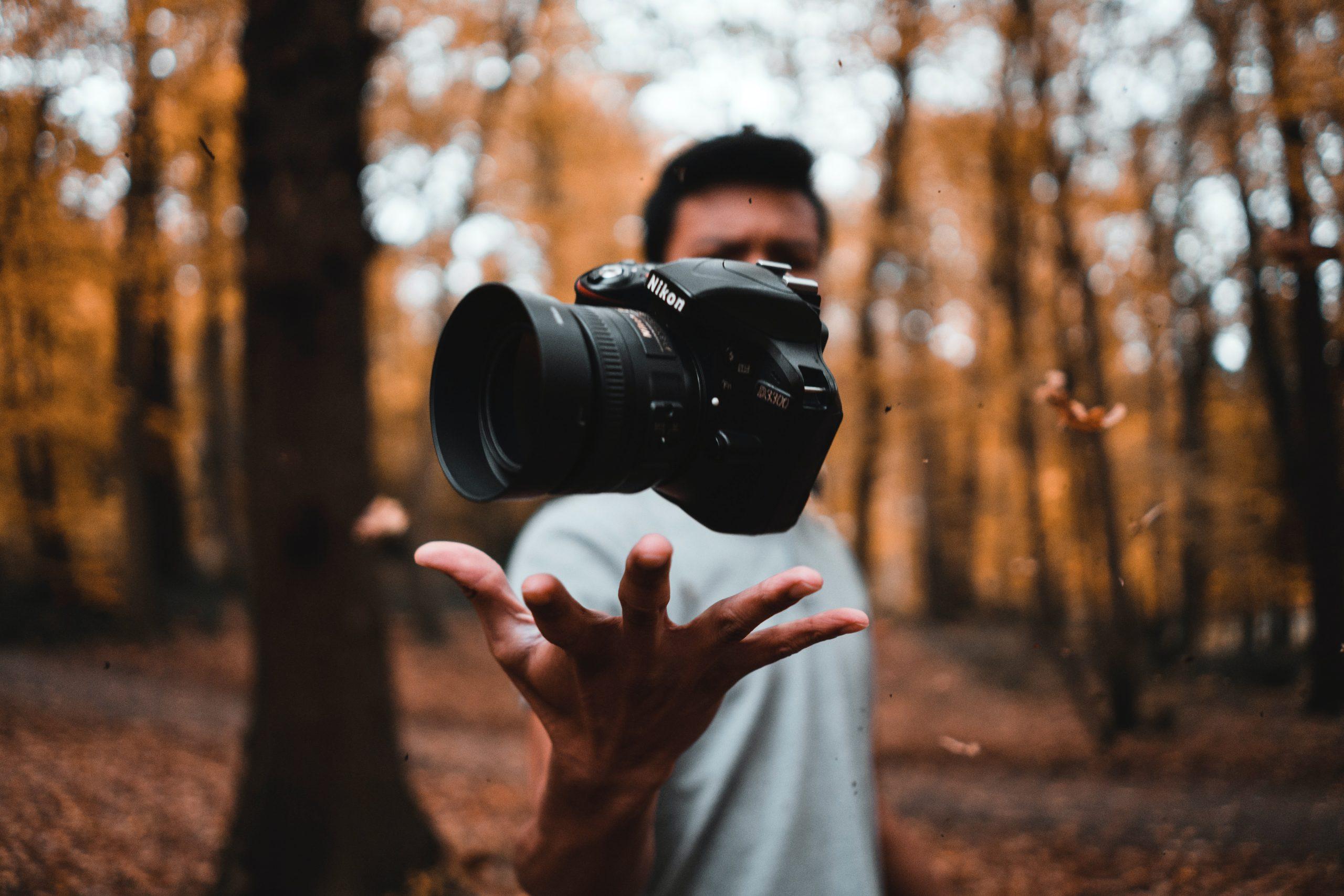 Imagem de um homem segurando uma câmera fotográfica digital.